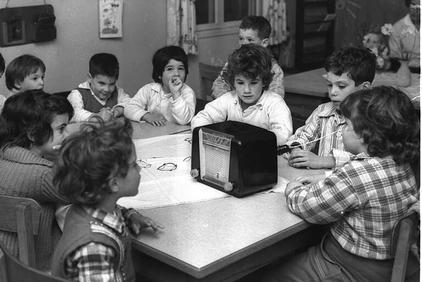 ילדי הקיבוץ (זיו, סמדר, גליה, ואחרים) מאזינים לרדיו בבית הילדים, 1962